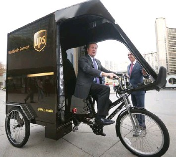 ?? STEVE RUSSELL/TORONTO STAR ?? Mayor John Tory checks out the new UPS cargo bike with Christoph Atz, UPS Canada president, at Monday's launch.
