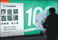 ?? PROVIDED TO CHINA DAILY ?? A man looks at a billboard of Zuoyebang in Shanghai on Dec 26. The online education startup raised $1.6 billion in its series E-plus round of funding in December.