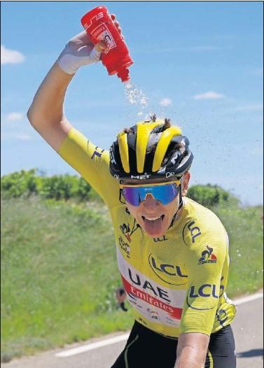 ??  ?? Tadej Pogacar bromea con el fotógrafo en carrera al echarse encima un bidón de agua debido al calor.