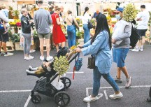?? JUSTIN TALLIS/AGENCE FRANCE-PRESSE /GETTY IMAGES ?? A London flower market on Sunday. A plan that England has now dropped was intended to incentivize coronavirus vaccinations.