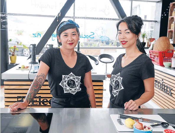 ??  ?? Then to now: Friends Dal Philavong, left, and Dai Phonevilay at a recent cooking class they ran at the Social Cooking school in Wellington.