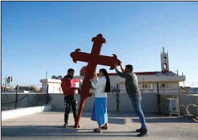 ?? HADI MIZBAN / AP ?? Iraqi Christians place a cross on a church in Qaraqosh, Iraq, Monday. Iraq's Christians are hoping that a historic visit by Pope Francis in March will help boost their community's struggle to survive. The country's Christian population has been dwindling ever since the turmoil that followed the 2003 U.S.-led invasion.