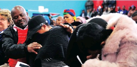 ?? Picture: PHANDO JIKELO ?? DISTRAUGHT: James Ndabeni, a cousin of the late DA councillor Xolile Gwangxu, comforts his sisters at a memorial service held in Lower Crossroads in Philippi.