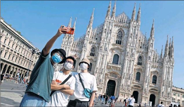 ??  ?? Milán vuelve a sonreír después de haber sido una de las zonas que inicialmente se vieron más afectadas en la pandemia. En la imagen, unos turistas ayer frente al Duomo.