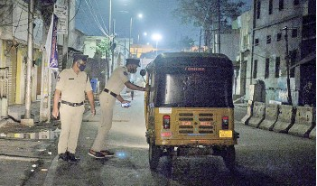 ?? — AFP photos ?? Police personnel checks an auto rikshaw along a deserted road during a night curfew imposed by the state government amidst rising Covid-19 coronavirus cases in Hyderabad.