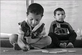 ?? Yesica Fisch/The Associated Press ?? Mustafa, left, draws on a piece of paper next to another child in a tent, at the Khazer refugee camp in east Mosul, Iraq.