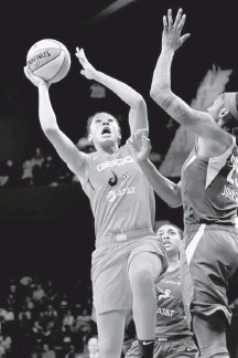 ?? KATHER­INE FREY/THE WASH­ING­TON POST ?? Wash­ing­ton's Aerial Pow­ers shoots over Glory John­son of Dal­las in the se­cond half of her 18-point out­ing against her former team.
