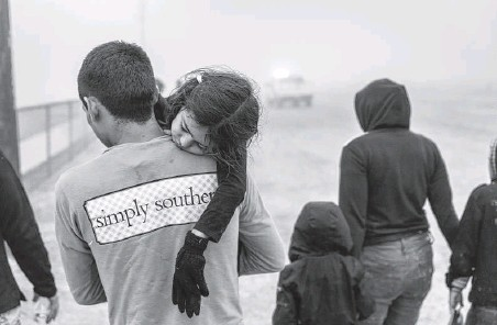 ?? John Moore / Getty Images ?? Central American families walk toward Border Patrol agents Saturday near the Texas-Mexico border at La Joya. ICE says an $86.9 million contract with Endeavors Inc. provides about 1,200 hotel beds where families generally stay less than 72 hours for processing.