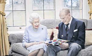 ?? PHOTO: HAND­OUT VIA GETTY IM­AGES ?? From the fam­ily . . . Queen El­iz­a­beth II and Prince Philip, Duke of Ed­in­burgh look at a home­made wed­ding an­niver­sary card, given to them by their great­grand­chil­dren Prince Ge­orge, Princess Charlotte and Prince Louis, in the Oak Room at Wind­sor Cas­tle this week.