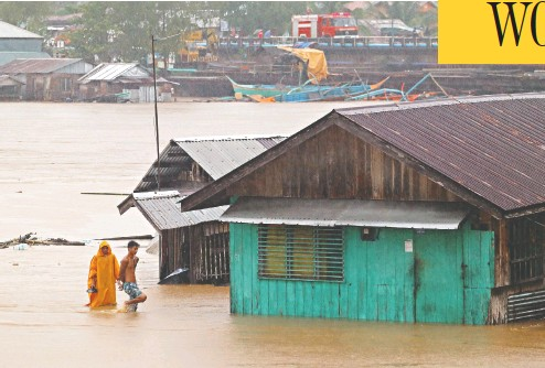 ?? ERWIN MASCARINAS / AFP VIA GETTY IMAGES ?? Residents walk past flooded houses near a river in Tandag City, Philippines, swollen by tropical storm Dujuan.