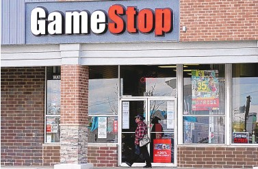 ?? NAM Y. HUH/ASSOCIATED PRESS ?? A woman walks past a GameStop store in Des Plaines, Illinois, on Oct. 15. Two hedge funds are bowing out of their short positions on the money-losing video game retailer.