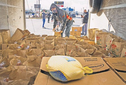 ?? CHRIS PIETSCH/ USA TODAY NETWORK ?? Volunteer Keiki Rauschenburg helps distribute Thanksgiving meals donated by Keith and Amy Lewis, who own the Once Famous Grill and Quacker's Last Stop sports bar in Eugene, Ore.