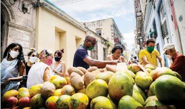 ?? Foto: dpa/AP/Ramon Espinosa ?? Menschen mit obligatorischen Schutzmasken beim Kauf von Mangos in Havanna