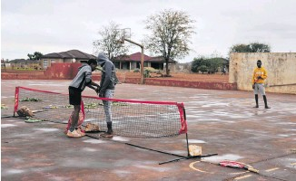 ??  ?? After a light thundershower boys prepare to play tennis in Thomo village near Giyani in Limpopo.