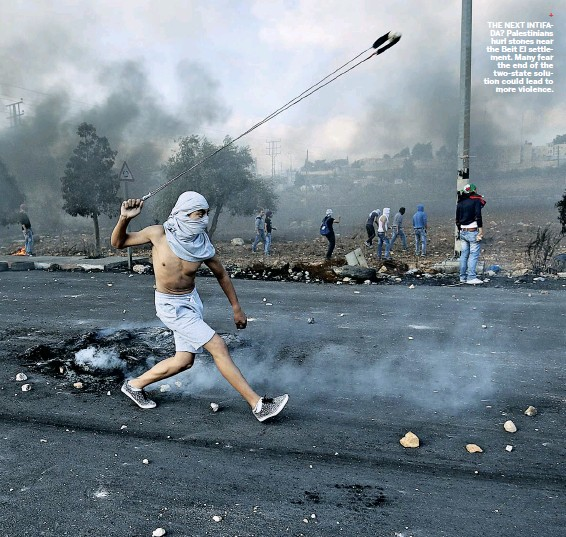 ??  ?? THE NEXT INTIFADA? Pales­tini­ans hurl stones near the Beit El set­tle­ment. Many fear the end of the two-state solution could lead to more vi­o­lence.