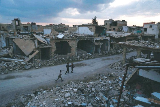 ?? SAMEER AL-DOUMY/AGENCE FRANCE-PRESSE VIA GETTY IMAGES ?? ABOVE: Children walk past destroyed buildings in Douma, not far from Damascus, the capital. Both sides of the conflict exchanged allegations of violations, but mostly there was widespread relief.