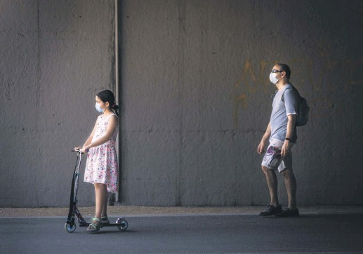 ??  ?? A little girl wearing a protective face mask rides an electric scooter as her father walks behind her through Madrid Rio Park amid the coronavirus outbreak, Madrid, Spain, May 25, 2020.