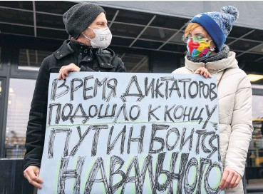 ?? PHOTO: REUTERS ?? Making their feelings known . . . A couple hold a banner reading ''Dictator's times come to an end, Putin is scared of Navalny'' as they wait for the arrival of Russian Kremlin critic Alexei Navalny outside Terminal 5 of Berlin Brandenburg Airport last week.