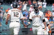 ??  ?? The Giants' Alex Dickerson, left, celebrates his home run with teammate Brandon Belt against the Rockies on Sunday at Oracle Park in San Francisco.