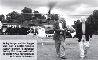 ?? Staff photo By Cecil Anderson ?? Roy Morgan and Don Ruggles walk from a LifeNet helicopter Tuesday afternoon at Northridge Country Club during a celebration for LifeNet Air's 30 years of service.