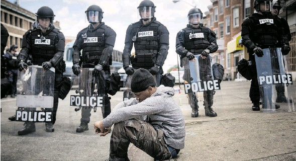 ?? ANDREW BURTON/GETTY IMAGES ?? Daquan Green, 17, sits on the curb in Baltimore as riot police stand guard after rioting following Freddie Gray's funeral. Gray died while in police custody.