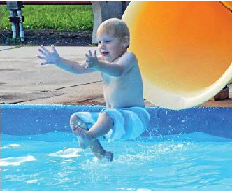 ?? News-Herald photo — DEBBY HIGH ?? Levi Wenger, 3, slides down into the pool at the Burger & Birch event at the Holiday House Recreation Center Friday, July 19.