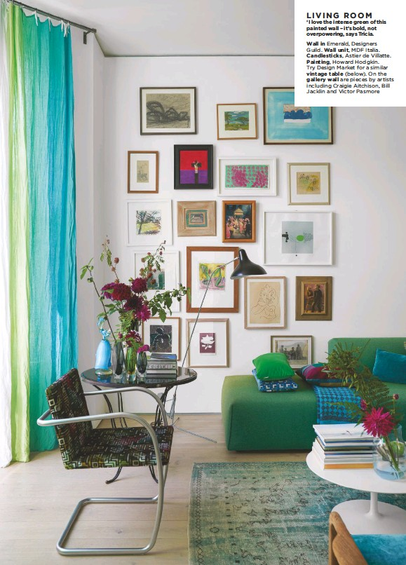 ??  ?? LIVING ROOM 'I love the intense green of this painted wall – it's bold, not overpowering, says Tricia. Wall in Emerald, Designers Guild. Wall unit, MDF Italia. Candlesticks, Astier de Villatte. Painting, Howard Hodgkin. Try Design Market for a similar vintage table (below). On the gallery wall are pieces by artists including Craigie Aitchison, Bill Jacklin and Victor Pasmore