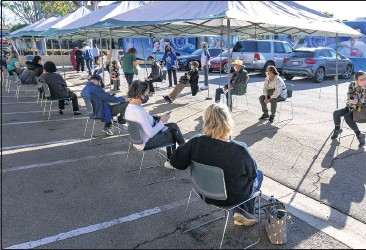 ?? PHOTOS BY MARK RIGHTMIRE — STAFF PHOTOGRAPHER ?? Seated socially distant apart, people get their vitals taken before receiving their COVID-19 vaccination on Thursday in the parking lot at Families Together of Orange County Community Health Center, located on First Street in Tustin.