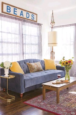 """??  ?? top: EMILY'S VINTAGE-STYLE SOFA IS FROM NOVOGRATZ, available at Walmart. """"I think the bead sign truly just came from an old bead store,"""" she says. As for the shiny side table, """"I wanted to incorporate some brass in this room, as I like the texture and..."""