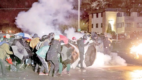 ?? — AFP photo ?? Demonstrators face off with police near the Brooklyn Center police station in Brooklyn Center, Minnesota.