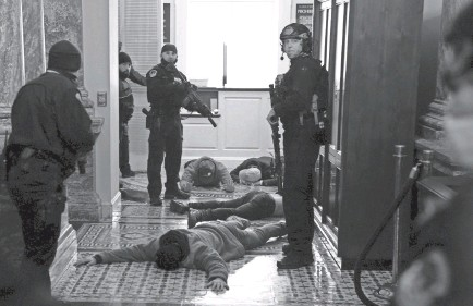 ?? DREW ANGERER/GETTY IMAGES ?? U.S. Capitol Police detain protesters at gunpoint outside of the House Chamber, where a joint session of Congress had been meeting Jan. 6 to confirm the votes of the Electoral College.