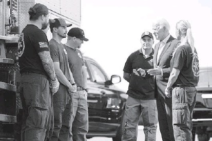 ?? EVAN VUCCI/AP ?? President Joe Biden greets firefighters as he tours the National Interagency Fire Center on Monday in Boise, Idaho.