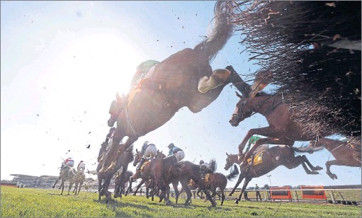 ?? Picture: David Davies/PA ?? Runners and riders clear a fence during the Ryanair Stayers Hurdle on Grand National Day at Aintree yesterday