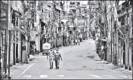 ?? SANJEEV VERMA/HT PHOTO ?? Civil defence personnel patrol a deserted street in Sadar Bazaar on Tuesday.