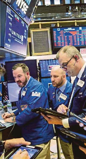 ?? AFP PIC ?? Traders at the New York Stock Exchange in New York City. United States President Donald Trump's announcement for new tariffs caused volatility in the markets last Friday.