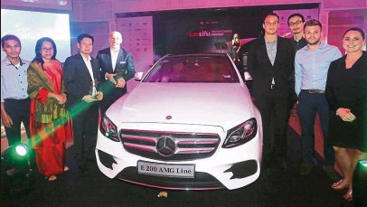 ??  ?? Mercedes-Benz Malaysia general manager Carsten Bauer (fourth from left) and his team posing with a Mercedes-Benz E-Class displayed in the ballroom during the gala dinner.