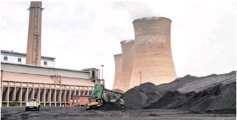 ??  ?? A worker supervises as a truck delivers coal supplies to the coal yard at the Grootvlei power station, operated by Eskom Holdings. All South African thermal power stations are sited on coal fields, consuming run-of-mine coal, says the writer.