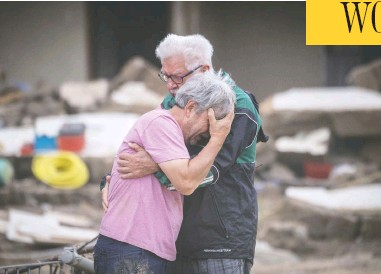 ?? BORIS ROESSLER / DPA VIA AP ?? Two brothers weep in each other's arms on Monday in front of their parents' house, which was destroyed by the flood in Altenahr, Germany. At least 165 people died and dozens are still missing in the floods that hit the western region.
