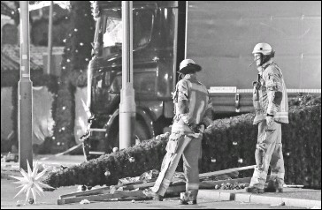 ?? MICHAEL SOHN / ASSOCIATED PRESS ?? Firefighters look at a toppled Christmas tree after a truck ran into a crowded Christmas market and killed 12 people Monday in Berlin, Germany.