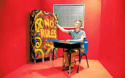 """?? PATRICK CONNOLLY/ORLANDO SENTINEL ?? Orlando Sentinel staffer Patrick Connolly sits in a booth modeled after a classroom with """"I will not take selfies in class"""" written on the chalkboard at Selfie WRLD Orlando in the Florida Mall on Thursday."""
