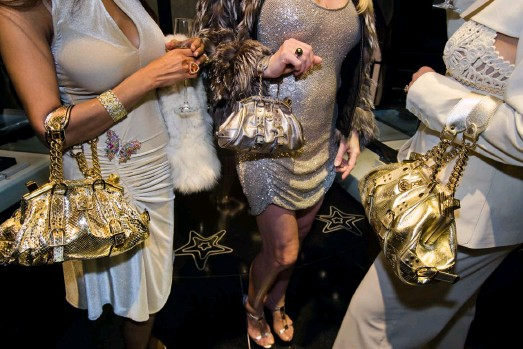 ??  ?? Lauren Greenfield: Jackie, 41, and friends with Versace handbags at a private opening at the Versace store, Beverly Hills, 2007. A Versace devotee, Jackie, shopped from monthly shipments of new merchandise that the design house sent to her home. Credit: Lauren Greenfield/INSTITUTE © Lauren Greenfield