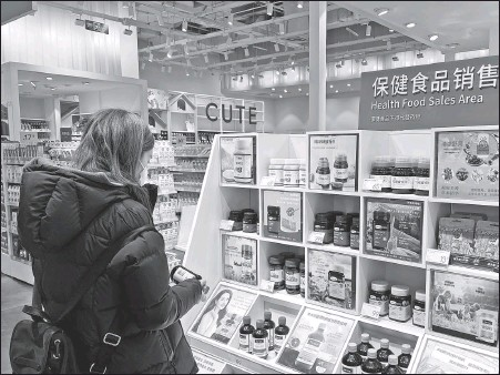 ?? PHOTOS PROVIDED TO CHINA DAILY ?? Above: A consumer browses nutrition products at the health food section at a Wanda Plaza in Beijing. Left: A visitor checks out imported ginseng products during the third China International Import Expo held in Shanghai in November.