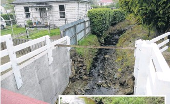 ?? PHOTOS: RICHARD DAVISON ?? Flood measure . . . A new culvert channelling the floodprone Hospital Creek runs beneath Campbelton St in Lawrence. Inset: This concrete block was among debris washed down Hospital Creek during a severe flood in July 2017.