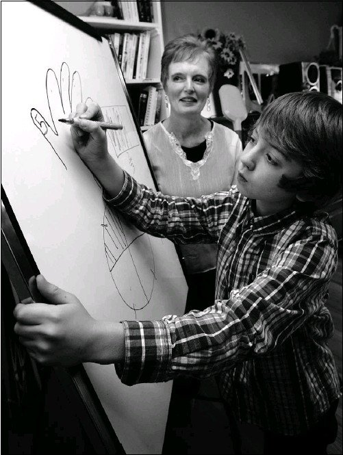?? Ted Jacob, Calgary Herald ?? Louise Ridout, founder of Education Wise, tutors nine-year-old Jace Kent at her facility in northwest Calgary.