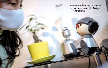 ?? — AFP photo ?? Hamaura talking Charlie in her apartment in Tokyo.
