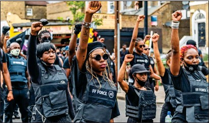 ??  ?? SALUTE: Protesters raise their fists in a black power-style gesture during yesterday's march, which blocked roads