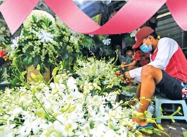 ??  ?? JUST LIKE 'UNDAS' – A vendor at the Dangwa Flower Market in Manila is busy preparing flower arrangements as demand soared early with many cemetery goers electing to visit their departed loved ones ahead of the closure order on all cemeteries, memorial parks, and columbaria on All Saints' Day and All Souls Day, which are still two weeks away. (Jansen Romero)