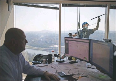 ??  ?? David Moon, owner of Moon Capital Management, works in his office as Murrin cleans the windows. Moon said he's used to the window cleaning and even makes faces to test Murrin. But the man doesn't budge, Moon said.