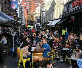 ?? (AP/Alberto Pezzali) ?? People gather outside cafes and pubs Monday in central London as some of Britain's coronavirus lockdown restrictions were eased by the government.