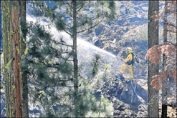 ?? Photographs by Rich Pedroncelli Associated Press ?? NEAR SOUTH LAKE TAHOE, a firefighter waters down a hot spot in the Kyburz fire. The blaze, in heavy timber along steep canyon walls, shut down a portion of Highway 50 linking Sacramento and Reno, Nev.